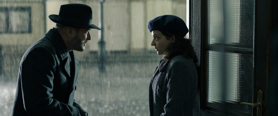 Noirish detective in hat and coat talking to a girl in the rain